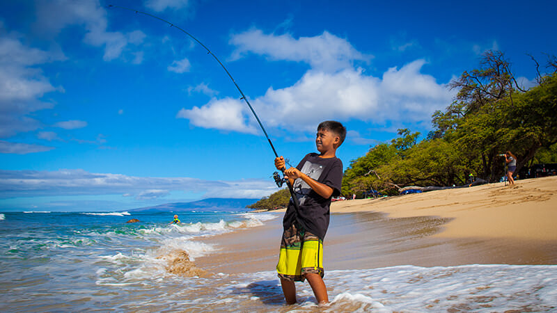 A boy fishing from a beach