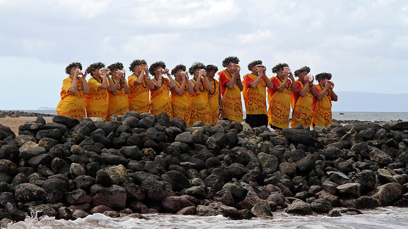 People in native Hawaiian dress blowing into conch shells