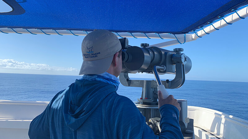 a man looks over the ocean through mounted binoculars