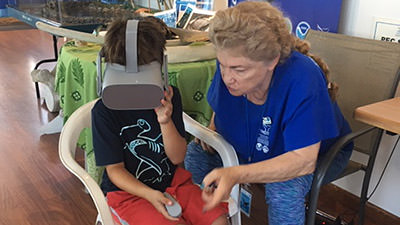 volunteer helping student with vr headset